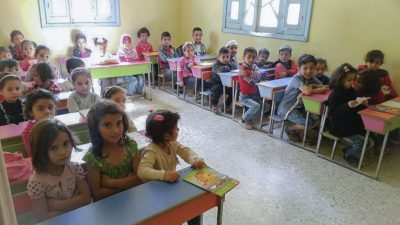 Children in a classroom in Raqqa, Syria, sitting at desks and looking at the photographer.
