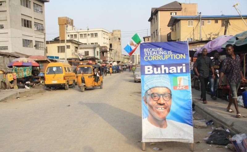 """Dans une rue au Nigeria, un panneau de campagne incite à voter Buhari avec le slogan: """"Parce que voler, c'est de la corruption""""."""