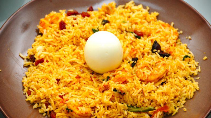 Un plat de biriyani : riz épicé, crevettes et un oeuf au centre.