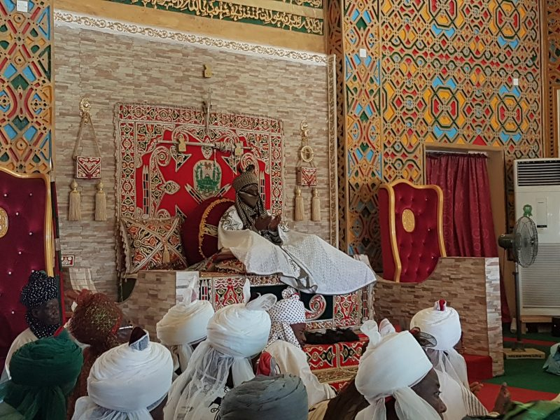 L'émir de Kano assis sur son trône tandis que plusieurs hommes portant des turbans blancs sont assis à ses pieds. Les murs du palais sont richement ornés de gravures.