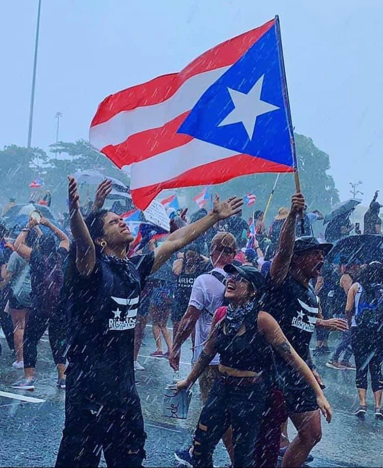 Protesters rejoicing in the rain on July 22 in San Juan, Puerto Rico. Image widely circulated on social media and taken from the Twitter account of social worker Larry Emil Alicea-Rodríguez.