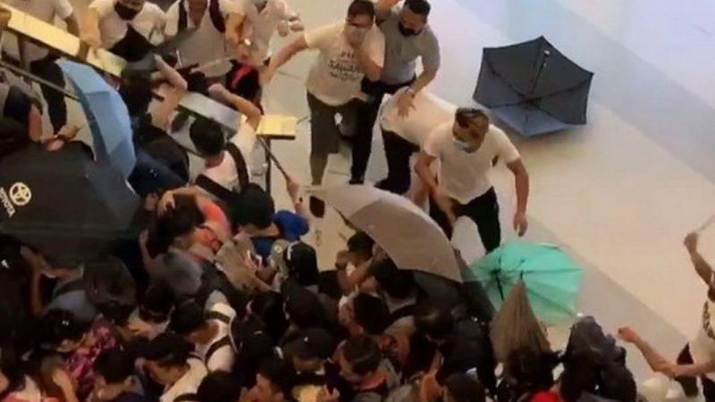 On distingue des personnes, paniquées, au bas d'un escalier, prises à partie par d'autres personnes. Ces dernières sont vêtues d'un t-shirt blanc, pantalon noir et d'un masque de protection faciale, et elles sont armées de bâtons. Les personnes sur l'escalateur essaient de leur échapper et sont serrées les unes contre les autres. Il y a des cris de peur. Certaines portent un parapluie ouvert, signe qu'elles ont participé à une manifestation. Elles se trouvent à l'intérieur d'une station de gare. Un parapluie est tombé sur le sol.