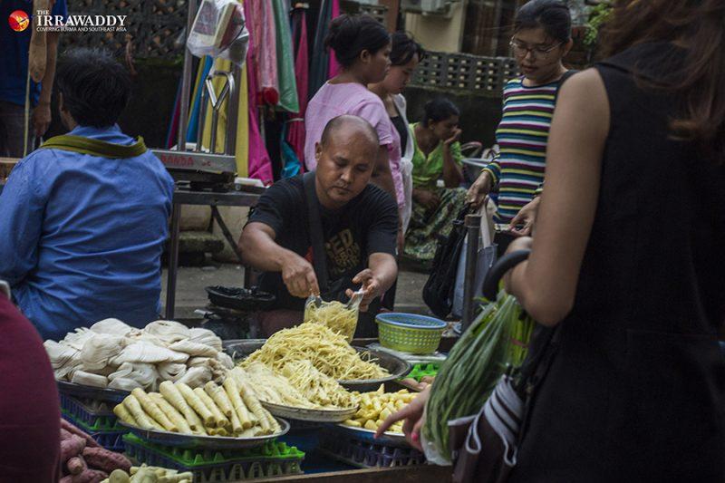 Un vendeur de rue emballe des pousses de bambou coupées en lamelles dans un sac plastique tandis qu'une cliente attend sa commande.