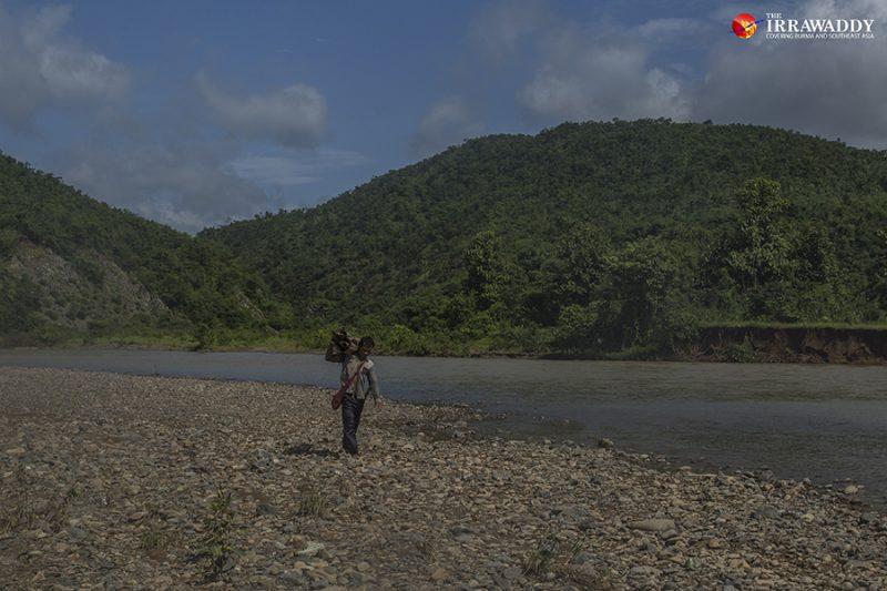 Un moissonneur porte ses pousses de bambou sur l'épaule et marche le long de la rivière.
