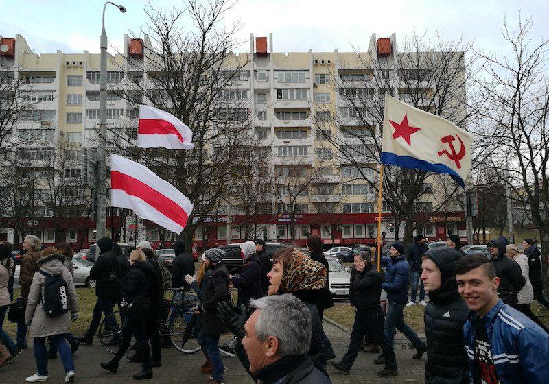 Des manifestant·e·s défilent dans rues de Minsk, brandissant des drapeaux biélorusses et soviétiques.