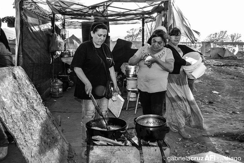 عائلات تطبخ في قدر مشترك لمشاركة الأهالي خلال احتجاج للدفاع عن حقوق الأرض، وتم النشر بموجب الموافقة.