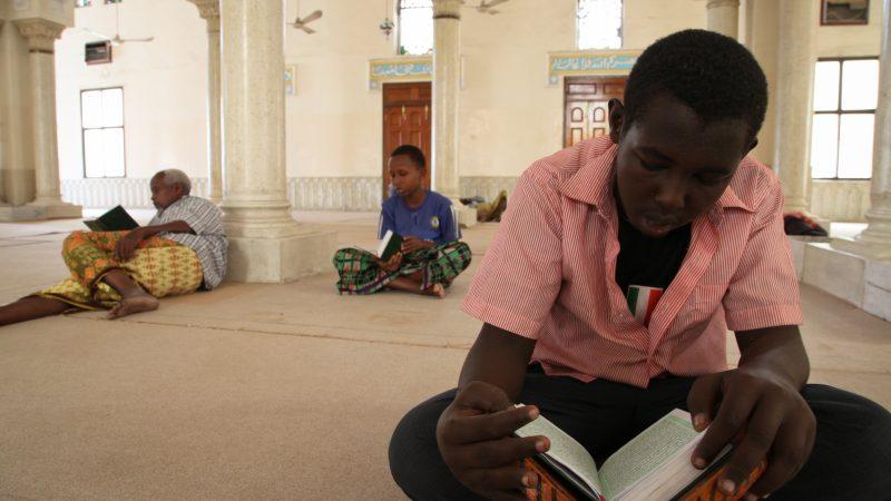 Photo de l'intérieur d'une mosquée à Mogadiscio, où deux enfants et un homme lisent le Coran.