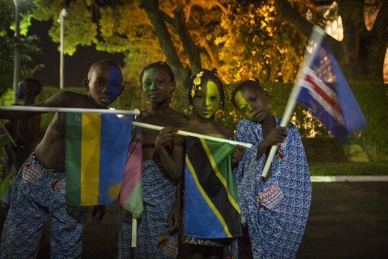 Des enfants portant les drapeaux du Rwanda, de la Tanzanie et du Cap-Vert.