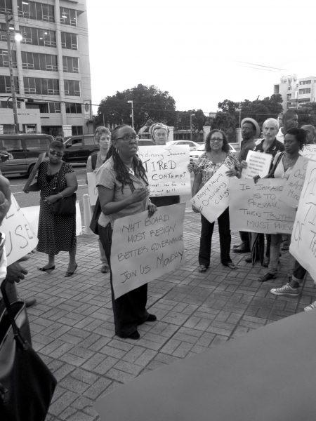 Jeannette Calder entourée de manifestant·e·s tenant des pancartes de protestation contre la mauvaise gouvernance