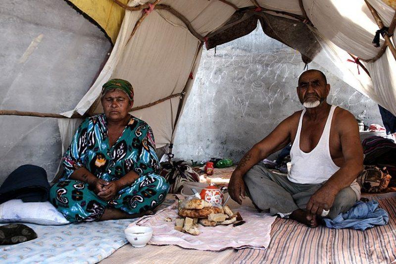 Sous une tente de fortune, un couple au regard triste partage du thé et du pain
