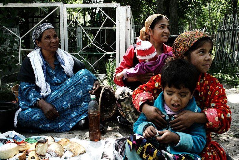 Assis par terre, enfants et adultes partagent un repas de pain, fromage et pâtisseries.