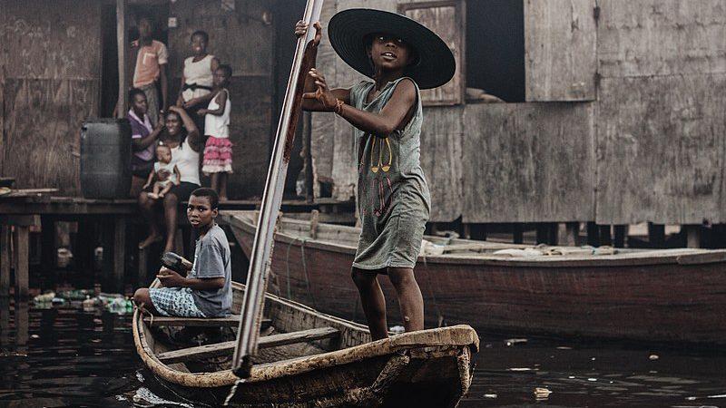 Deux enfants traversent le bidonville de Makoko à bord d'une pirogue.