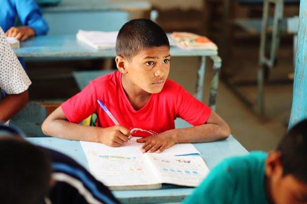 un élève concentré prend des notes dans un cahier au milieu de ses camarades de classe