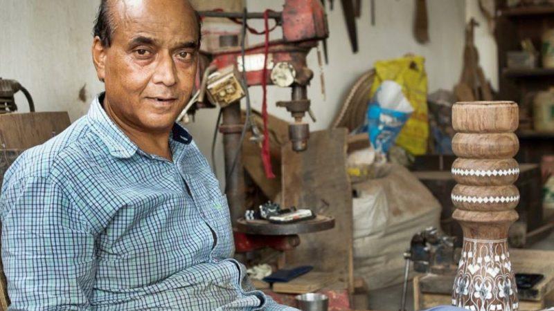 Rajesh, un sculpteur sur bois, photographié dans son atelier. On voit derrière lui des pièces en cours de confection et des machines.