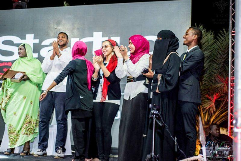 Alignés sur un podium, les jeunes innovateurs soudanais applaudissent en souriant.