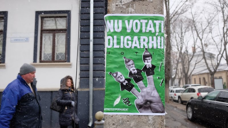 """Affiche sur un poteau dans une rue de Chișinău. Trois pantins représentant les """"oligarches"""" sont tenus sur les doigts d'une main."""
