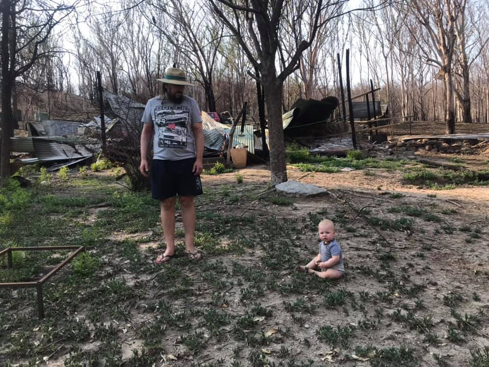 Storm Sparks' partner and son Zeke at their burnt-out property