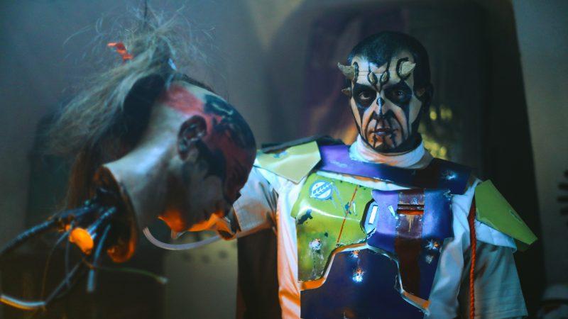 Un personnage au visage maquillé de noir et de blanc, portant des cornes, tient une tête coupée dont dépassent des fils.
