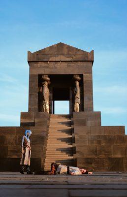 Le temple Jedi surplombe une scène où un personnage portant un foulard bleu observe un homme gisant à terre.
