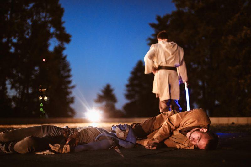 Un jedi s'éloigne avec son sabre laser, laissant derrière lui les cadavres de deux personnages gisant au sol. Au loin, une lumière éblouissante.