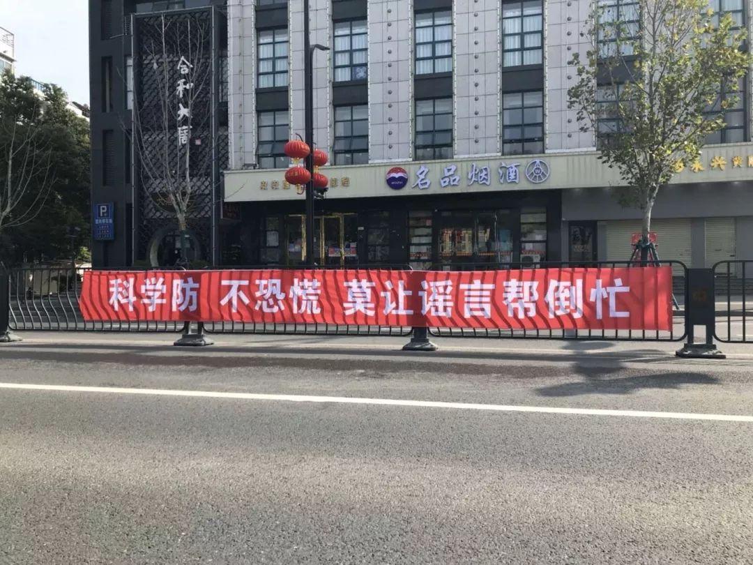 Dans une rue vide, une grande bannière exhorte les habitants au calme.