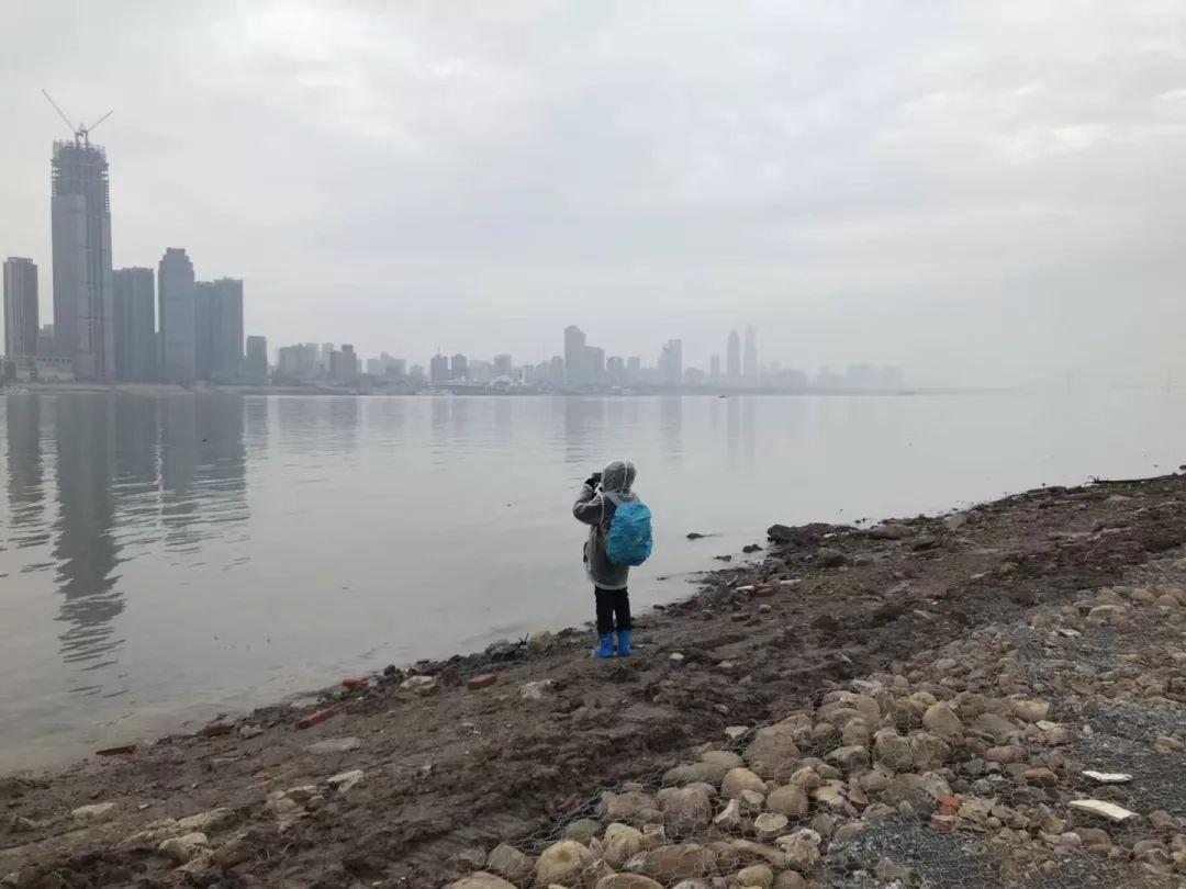 une personne prend des photos des gratte-ciels sur l'autre rive à Wuhan