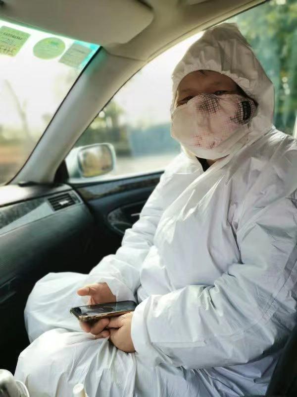 Ai Xiaoming dans une voiture, vêtue de la tête aux pieds d'une combinaison.