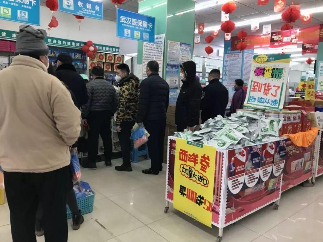 Des clients portant des masques attendent leur tour à la caisse.
