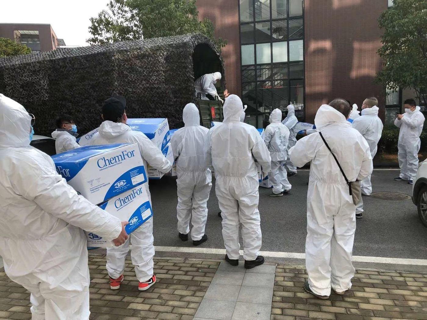 Un groupe de bénévoles en combinaison de protection se tient devant un hôpital, prêts à livrer les équipements
