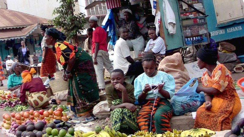 Des vendeuses devant un étal de légumes à même le sol.