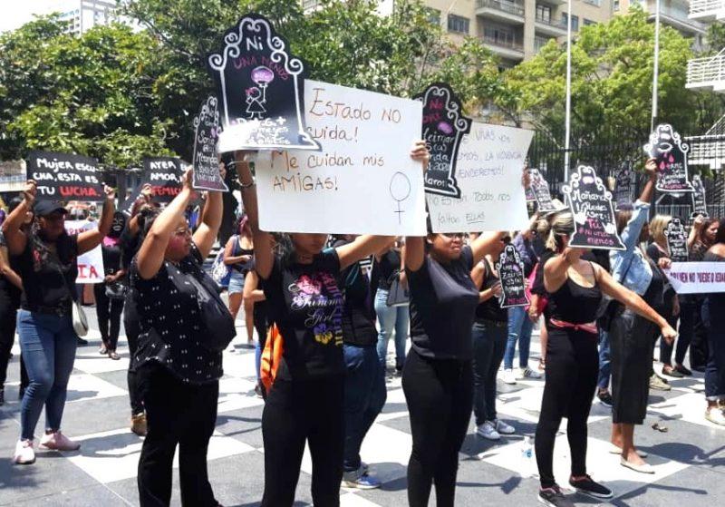 Um grupo de manifestantes empunha cartazes em forma de pedra tumular.