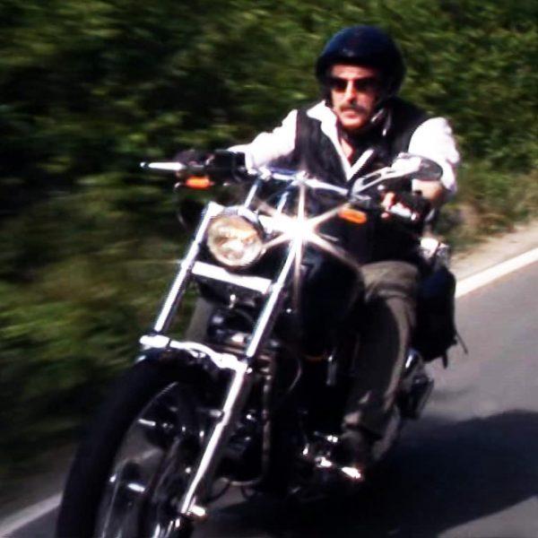 Giovanni Romanini, en moustache et lunette de soleil, aux commandes d'une moto puissante.
