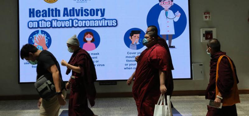 des moines bouddhistes portant des masques passent devant un immense panneau de prévention contre covid-19
