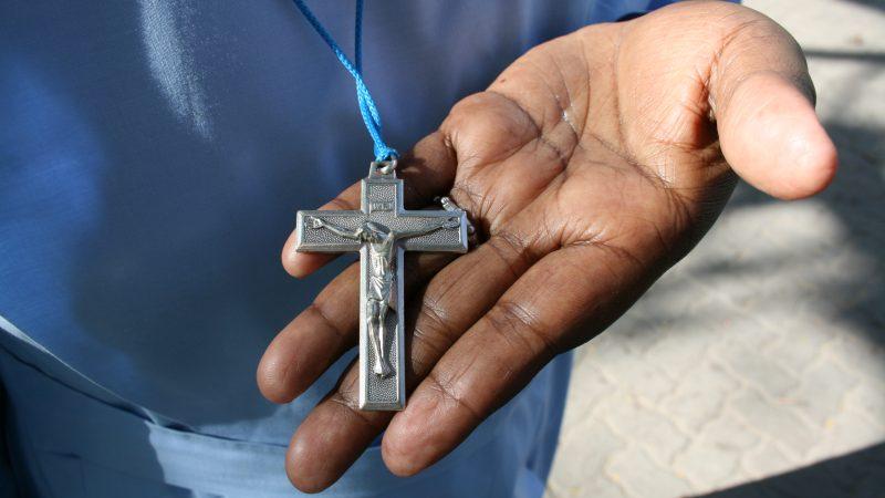 gros plan sur un crucifix entre les mains d'une religieuse