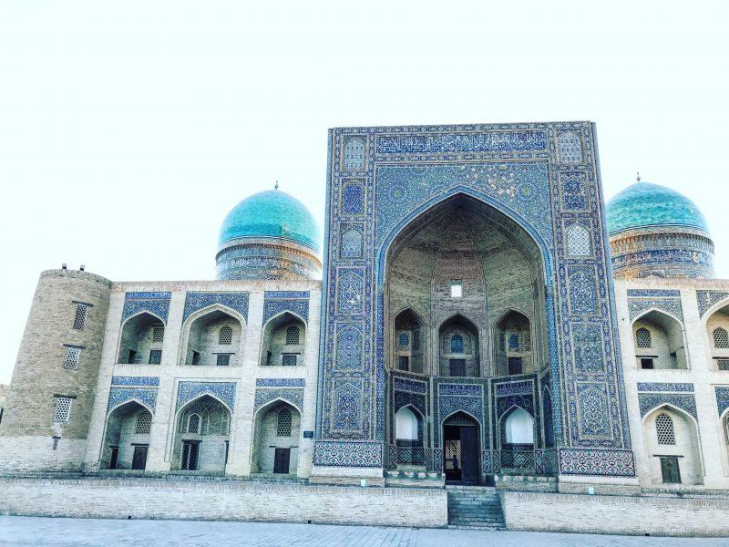 Façade d'une mosquée bleue avec une imposante entrée décorée de mosaïque aux tons bleus mer et turquoise, flanquée de deux dômes.