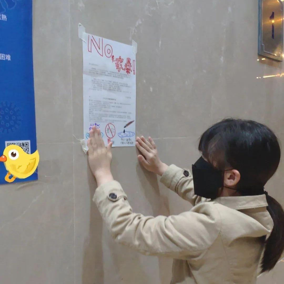 Une jeune fille portant un masque de protection faciale accroche une affiche sur un mur.
