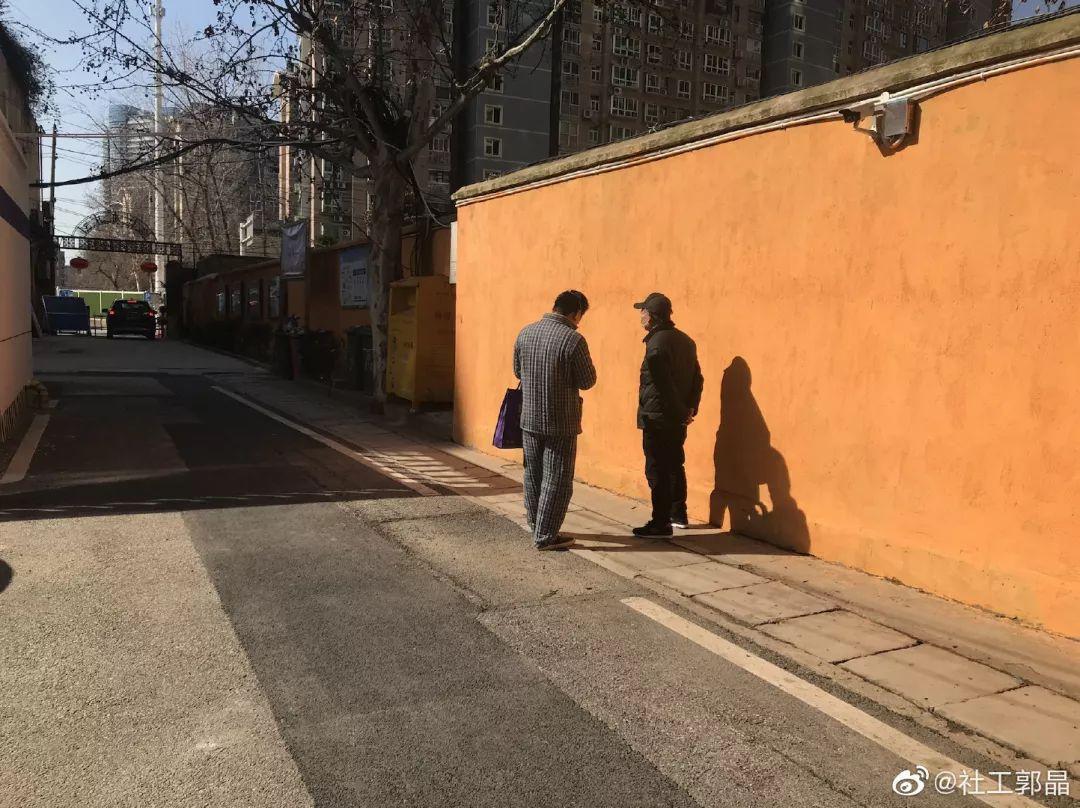 Deux hommes prennent le soleil dans une rue presque vide à Wuhan
