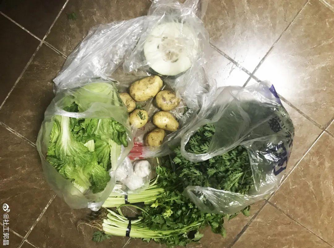 Un sac en platique posé sur le sol, rempli de légumes : pommes de terre, laitue, persil, concombre.