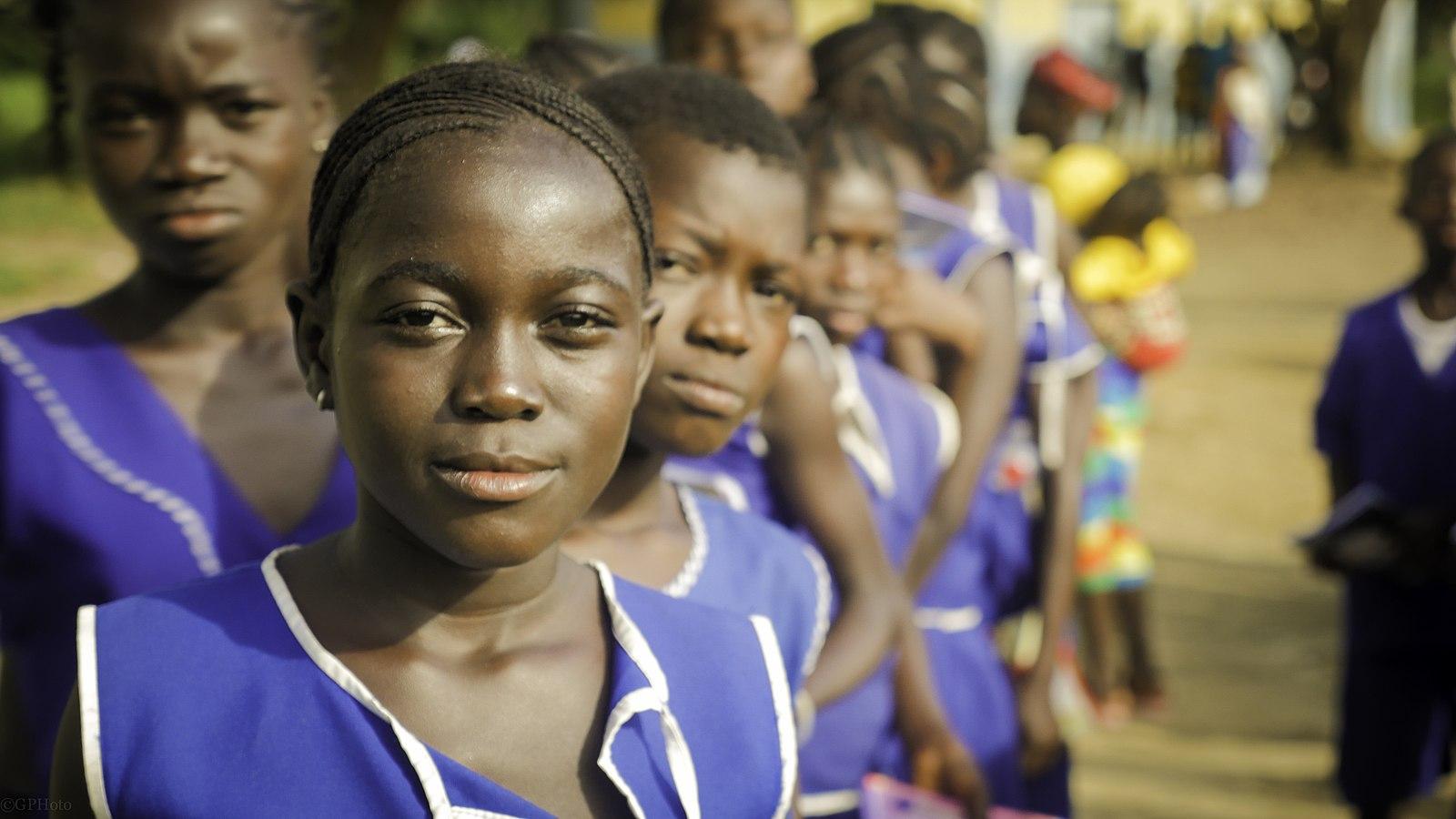 Une longue file d'élèves en uniforme devant une école en Sierra Leone.