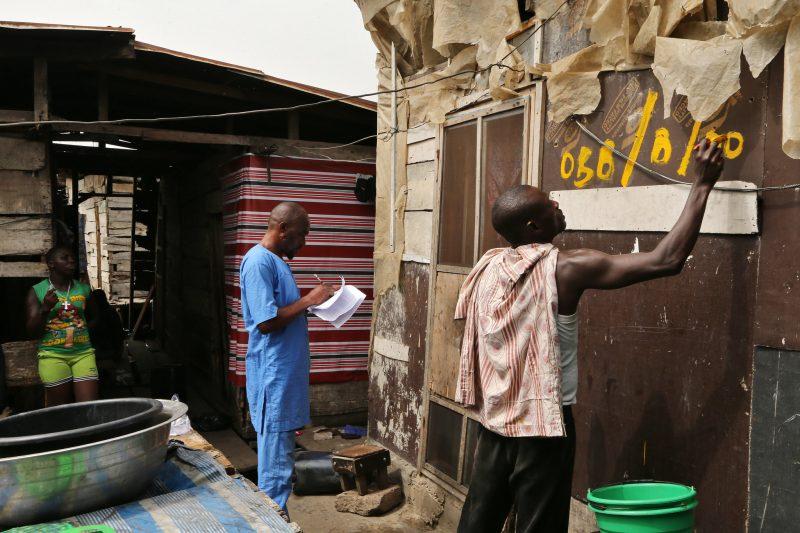 Dans un bidonville de Lagos, un homme prend des notes tandis que son collègue peint un numéro sur une maison
