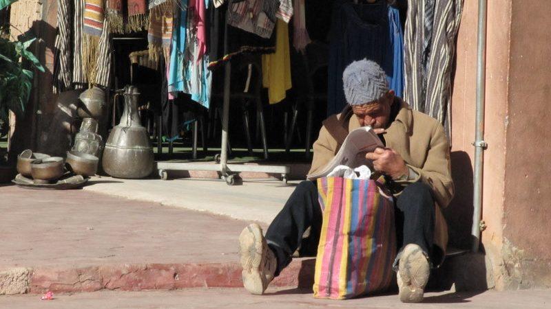 Un vieil homme assis par terre lit son journal dans un marché.