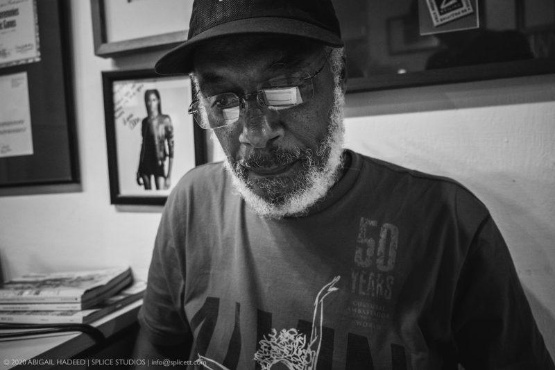 Tony Hall, en t-shirt et casquette, travaille sur son ordinateur, dont on aperçoit le reflet dans ses lunettes.