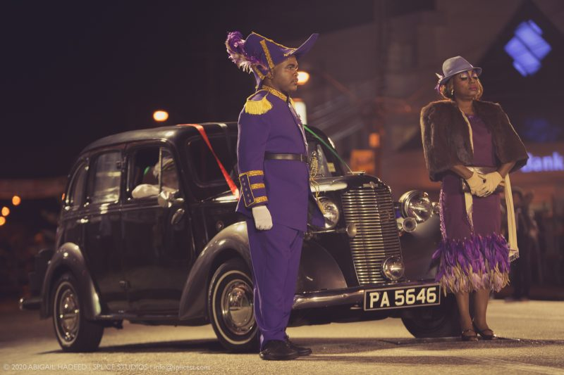 Les deux acteurs, vêtus de violet, se tiennent solennellement devant une voiture.