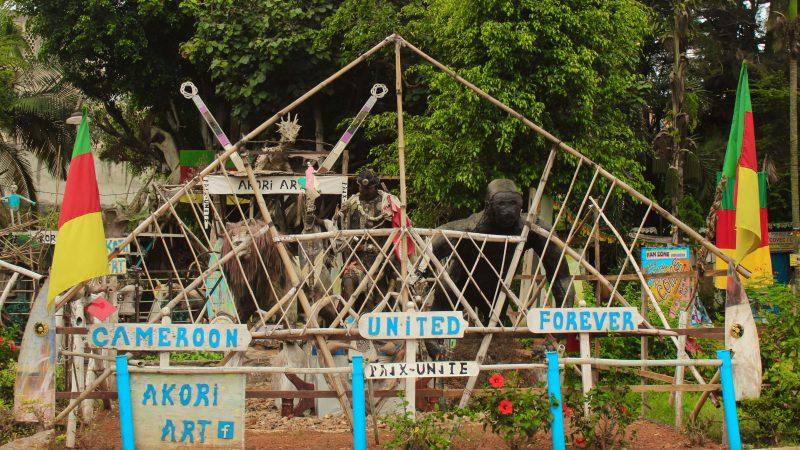 A l'entrée d'un parc au Cameroun, une barrière en bois tressé fait office de portail ; elle est encadrée par deux drapeaux du pays et porte l'inscription « Le Cameroun uni à jamais ». En arrière-plan, des statues représentant des animaux sauvages locaux : un gorille, une girafe et un lion.