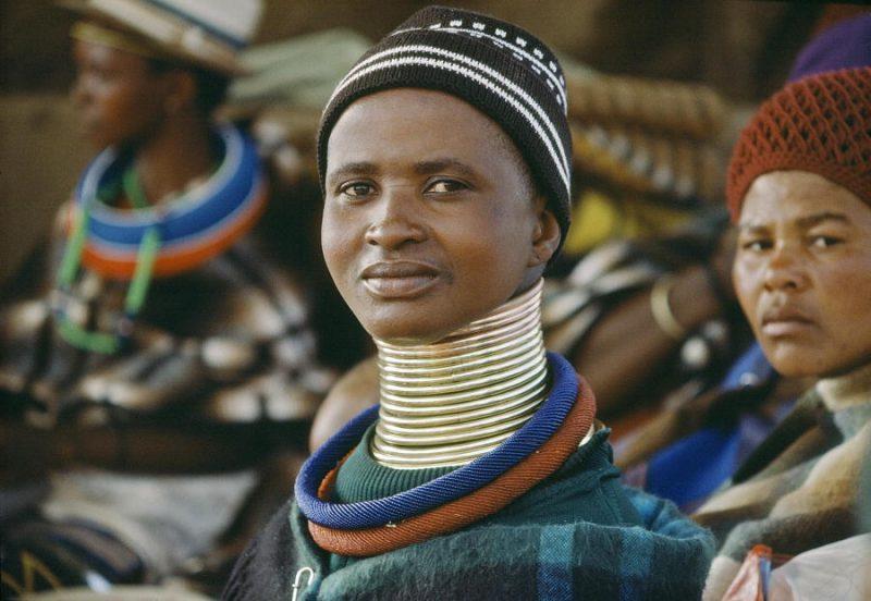 Femmes ndebele portant des bonnets, des vêtements chauds et des anneaux métalliques au cou.