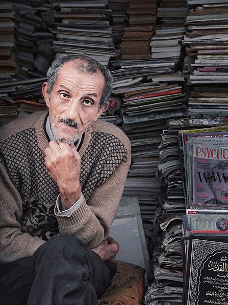 El-Abdi, pose devant sa boutique remplie de journaux et magazines du sol au plafond.