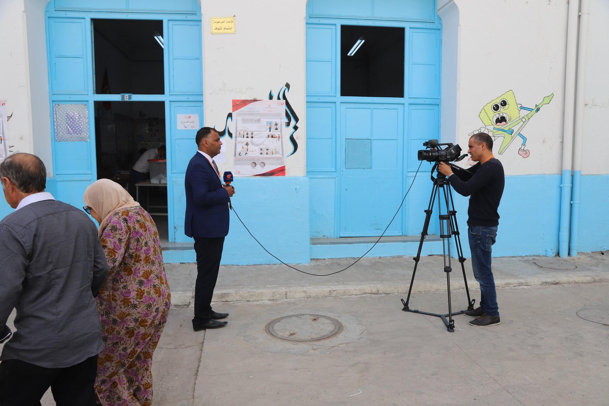 Un journaliste TV commente les élections devant un centre de vote en Tunisie.