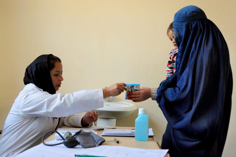 Hôpital Hootkhail, Afghanistan. Une femme médecin donne une boîte de médicaments à la fin de la consultation d'une femme qui porte un enfant dans les bras