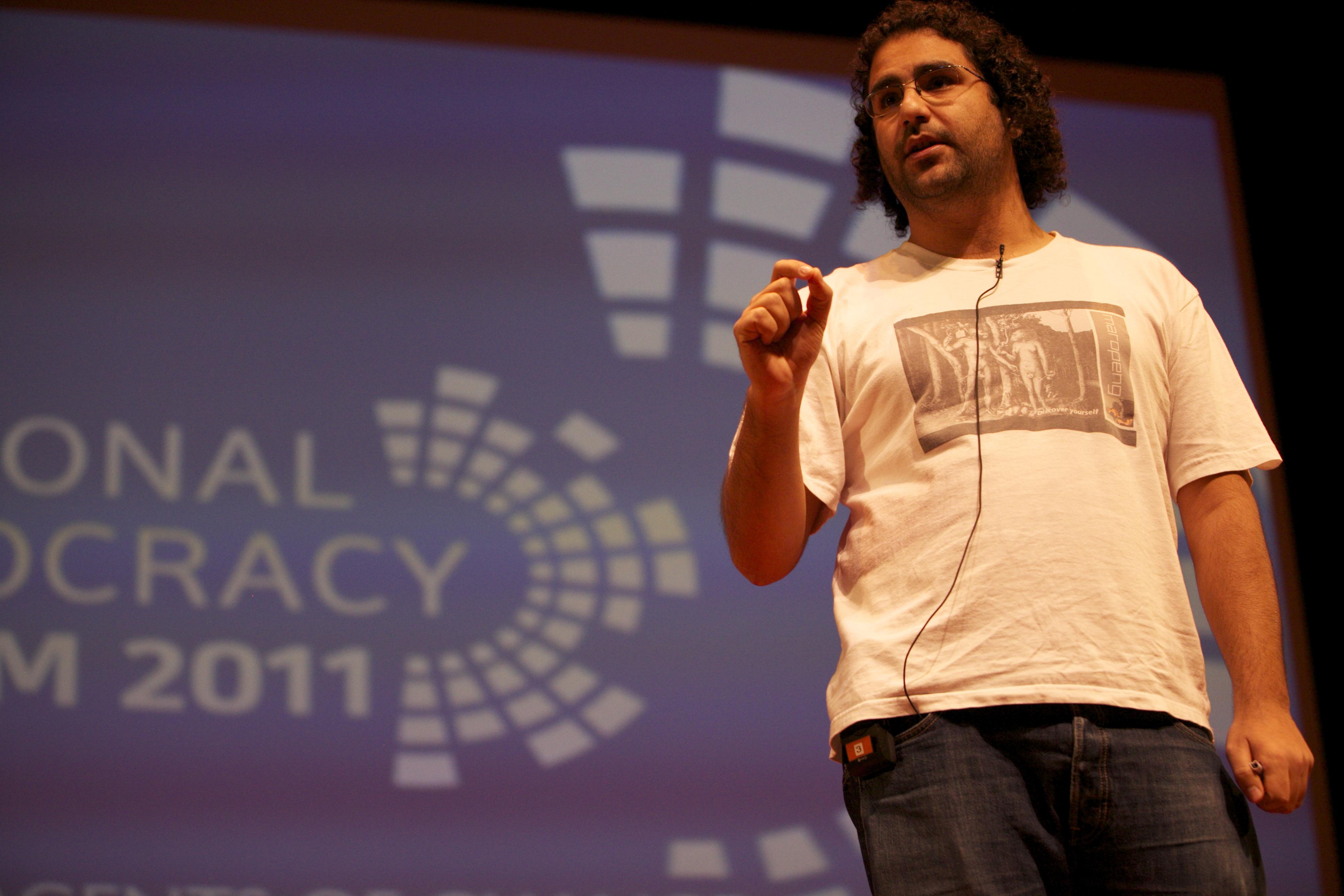 Alaa Abd El Fattah sur scène, devant le logo du Forum de la démocrate de 2011.