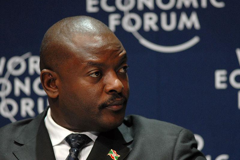 Portrait de Pierre Nkurunziza devant le logo du Forum économique mondial, avec un pins du drapeau burundais sur le revers de la veste.
